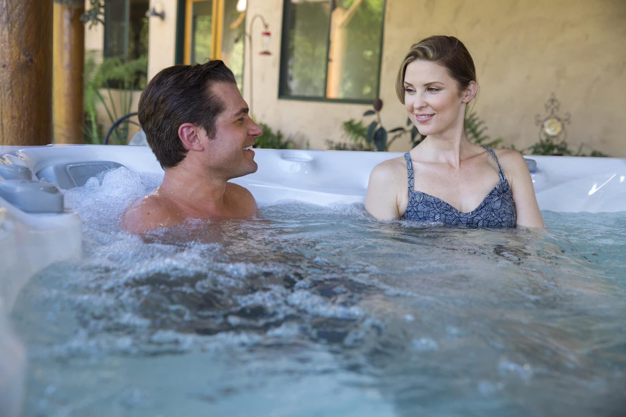 Man and woman soaking inside of a hot tub.